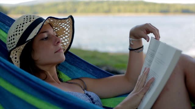 young woman reading book in the nature.close up - amaca video stock e b–roll