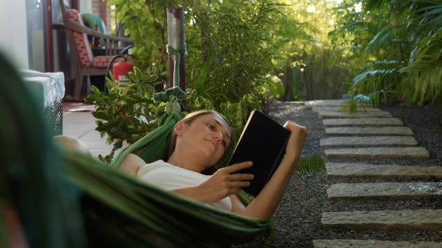 young woman reading book lying in hammock on terrace - amaca video stock e b–roll