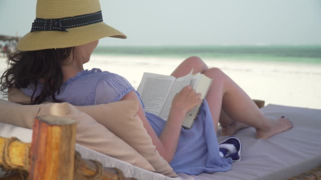 Young Woman Reading Book On White Beach By Ocean. Young woman is reading book on white sand beach by ocean. Adult caucasian girl in straw hat and sundress is lying on lounger sunbed in shadow on white sandy beach and reading book at bright sunny day. lounge chair stock videos & royalty-free footage