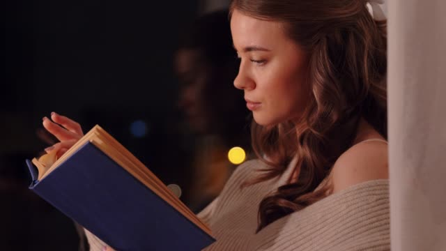 young woman reading book sitting at window - vídeo