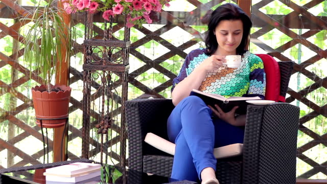 Young woman reading book while drinking coffee video