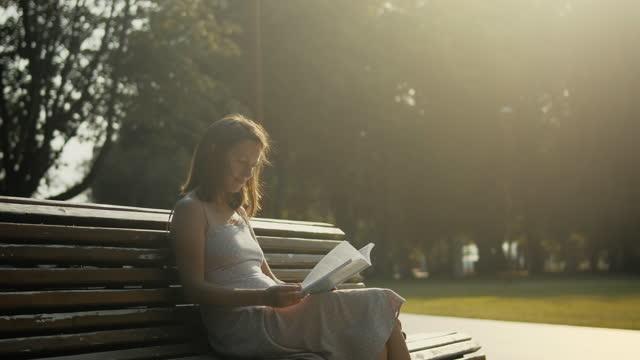 vídeos de stock e filmes b-roll de young woman reading in park at sunset - filosofia