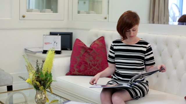 Young woman reading magazine video