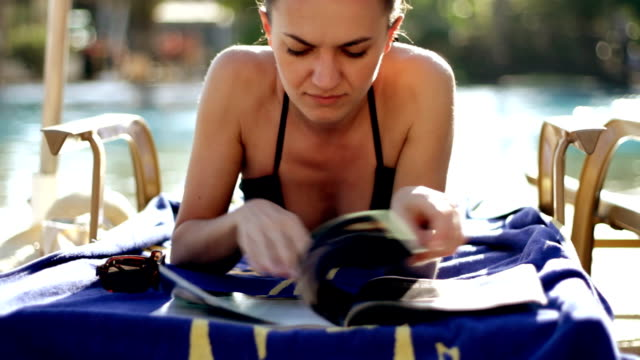 stockvideo's en b-roll-footage met young woman reading newspaper by the pool - newspaper beach
