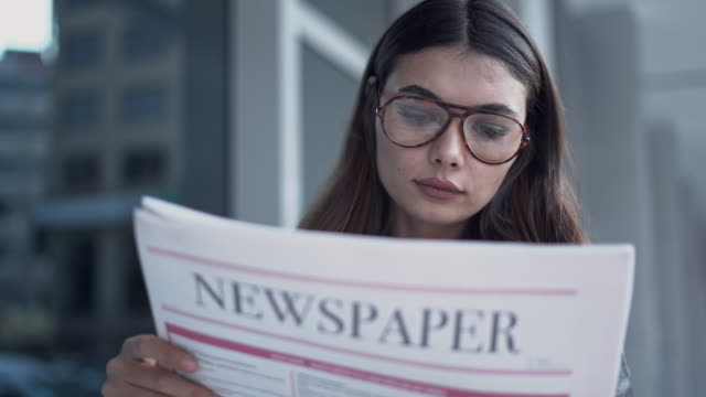 young woman reading newspaper in outdoors - newspaper paper video stock e b–roll