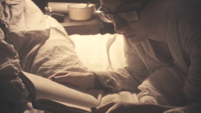 Young woman reading old book in bed - late night time video