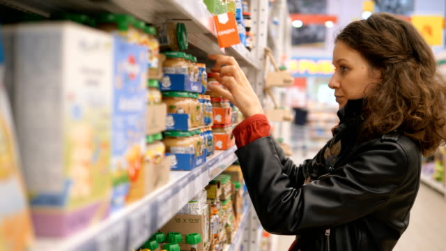 young woman reads concentrated composition on cans of baby food in a supermarket - paragone video stock e b–roll