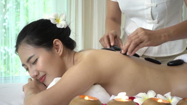 vídeos y material grabado en eventos de stock de joven recibe masaje y caliente spa piedra - tratamiento de spa