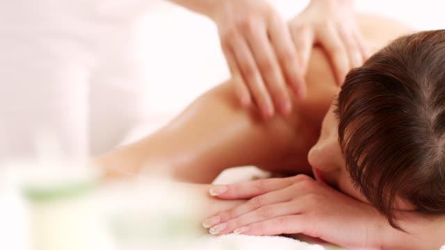 vídeos de stock e filmes b-roll de jovem mulher com massagem nas costas - tratamento em spa