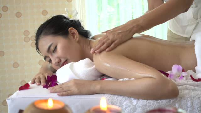 Young woman receiving back oil massage 4K resolution of Young beautiful asian woman receiving back oil massage from therapist look relax and enjoy spa in Thailand spa treatment stock videos & royalty-free footage