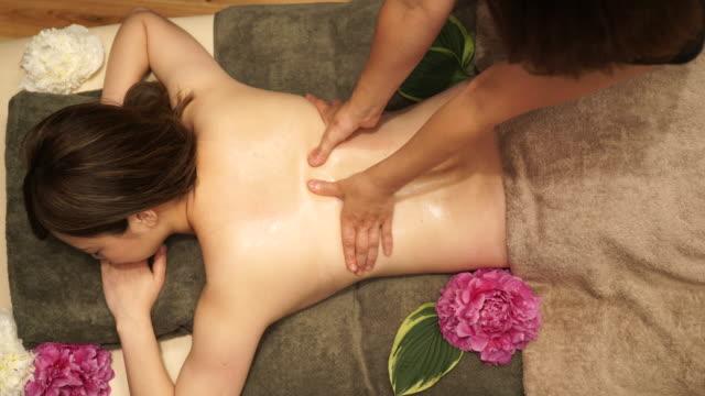 young woman receiving oil massage - zabieg spa filmów i materiałów b-roll