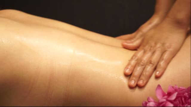 stockvideo's en b-roll-footage met jonge vrouw ontvangen olie massage - spa behandeling