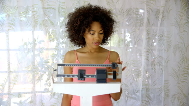 Young woman recording weight loss on scale video