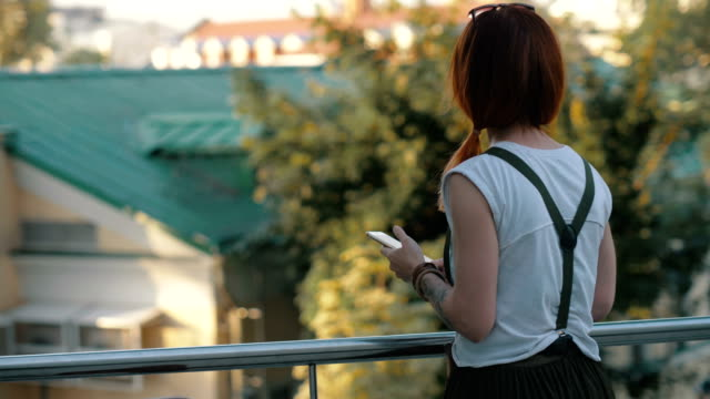 young woman red hair holding and using mobile phone back view - ragazza auricolari rossi video stock e b–roll