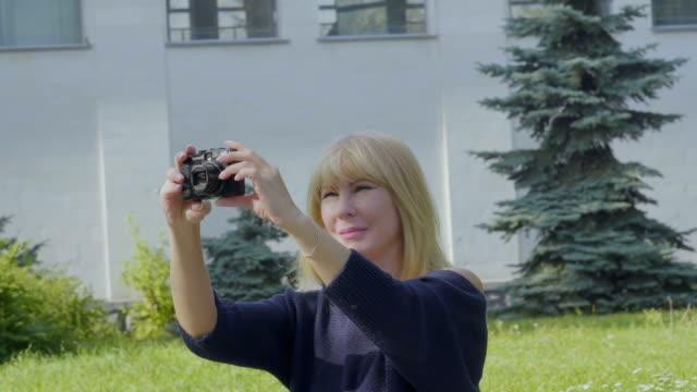 vídeos y material grabado en eventos de stock de mujer joven relajarse en manta en el parque y fotografías naturaleza alrededor de sí misma - memorial day weekend