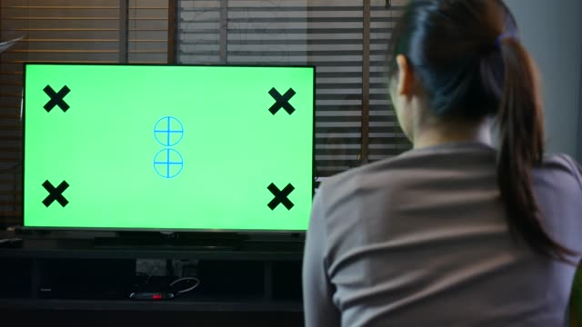 若い女性は家でテレビを見てゆっくりします。少女は緑色の画面のテレビを見てソファに座って - 通販点の映像素材/bロール