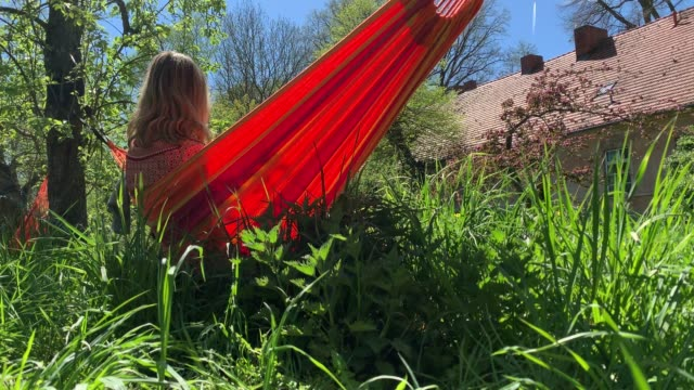 Young woman relaxes in hammock on a beautiful summer day Young woman relaxes in hammock on a beautiful summer day in a green open park ornamental garden stock videos & royalty-free footage