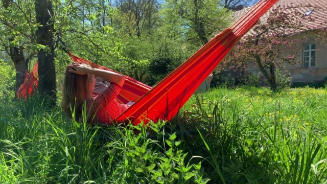 young woman relaxes in hammock on a beautiful summer day - amaca video stock e b–roll