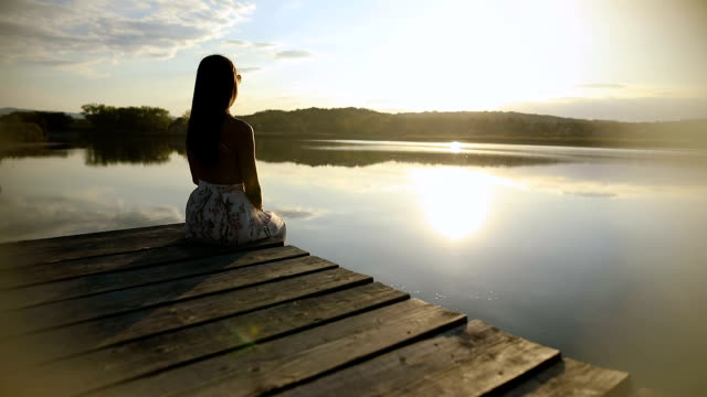 Young woman relaxes on lake pier, watches sunset through her sunglasses.Beautiful autumn day video