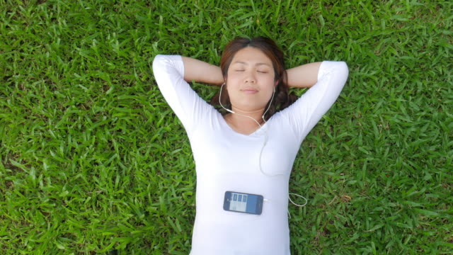 Young woman Relaxing and listening to music on green grass video