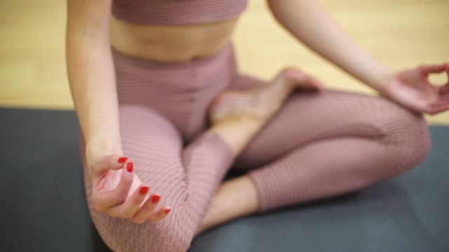 young woman relaxing and meditating in lotus pose with free space and copy space - posizione corretta video stock e b–roll