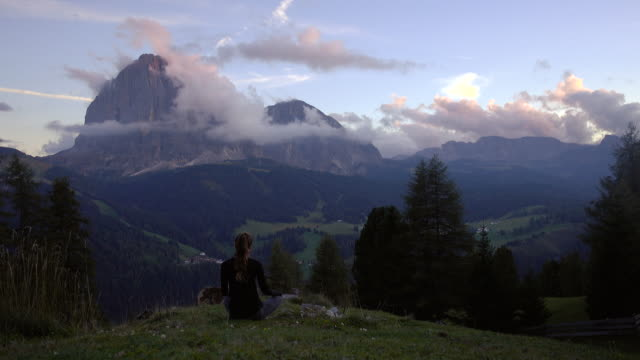 Young woman relaxing at sunset with a scenic view over Dolomites mountains