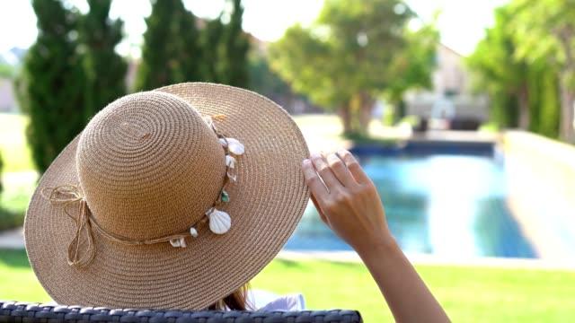 vidéos et rushes de jeune femme se relaxant à la piscine, concept de vacances d'été - chapeau