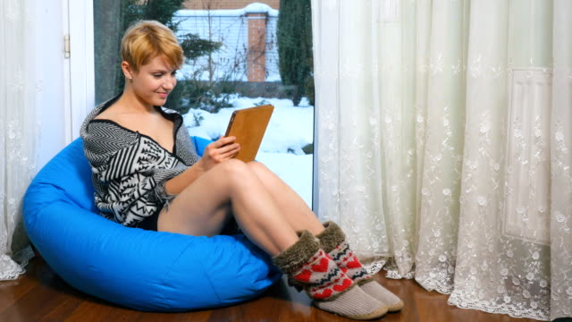 Young woman relaxing in bean bag with tablet near the window video