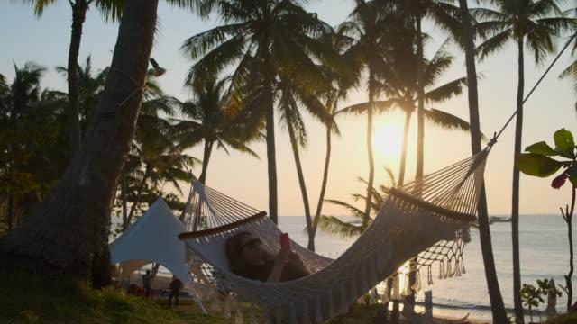 Young woman relaxing in hammock near the sea in tropics - video