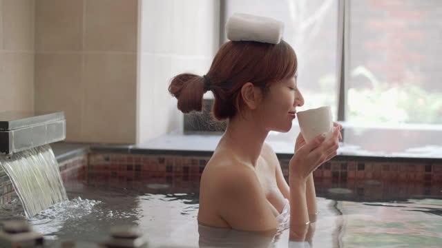 ung kvinna avkopplande i varma våren och dricka te - japanese bath woman bildbanksvideor och videomaterial från bakom kulisserna
