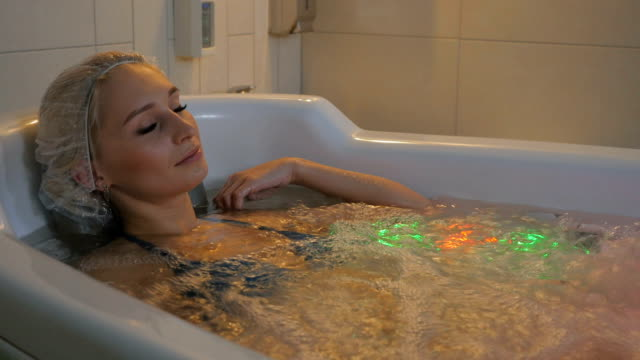 young woman relaxing in hydrobath with multicolored lights - china drug video stock e b–roll