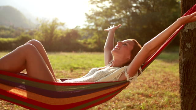 Young woman relaxing on hammock, arms outstretched video