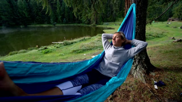 Young woman relaxing on hammock by the lake, Switzerland video