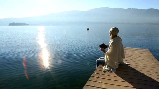 Young woman relaxing on lake pier with digital tablet video