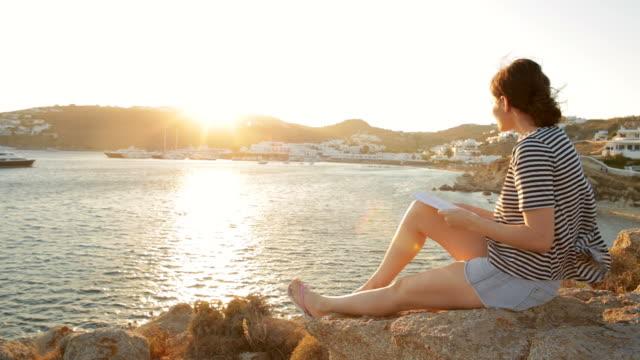 stockvideo's en b-roll-footage met jonge vrouw ontspannen tijdens het lezen van een boek bij zonsondergang. - literatuur