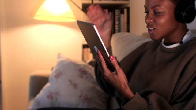 young woman relaxing with a digital tablet at home. - krótkie włosy filmów i materiałów b-roll