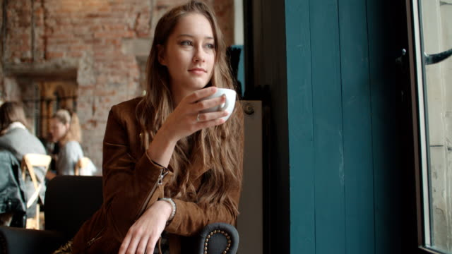 Young woman relaxing with cup of coffee in cozy restaurant. video