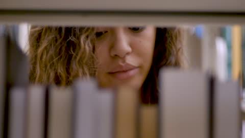 vídeos y material grabado en eventos de stock de mujer joven quita un libro de la estantería y comienza a leerlo - de cerca - estudiante