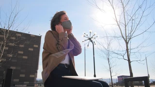 молодая женщина снимает медицинскую маску с лица - covid testing стоковые видео и кадры b-roll