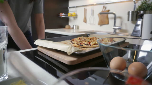 junge frau, die hausgemachte pizza aus dem ofen entfernen - selbstgemacht stock-videos und b-roll-filmmaterial