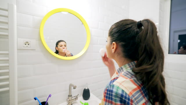 Young woman removing make-up in bathroom. video
