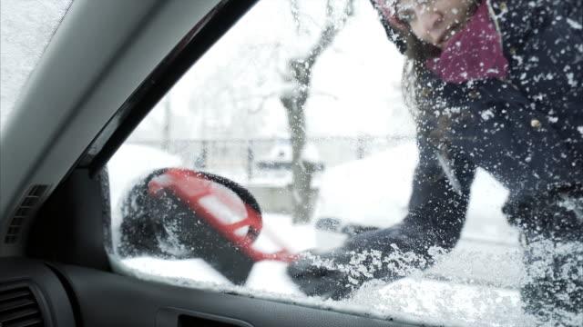vidéos et rushes de jeune femme, enlever la neige hors de la fenêtre de la voiture et le miroir. - raclette