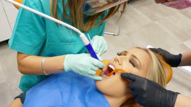 歯医者で歯を修復する若い女性 - 矯正歯科医点の映像素材/bロール