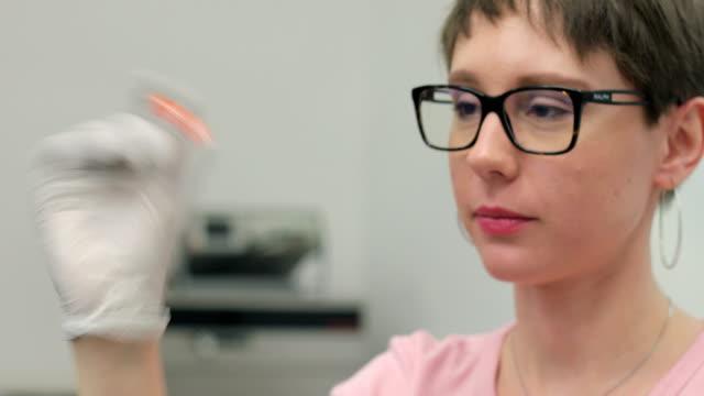 vídeos de stock, filmes e b-roll de jovem pesquisador agitando amostra científica em laboratório - amostra científica