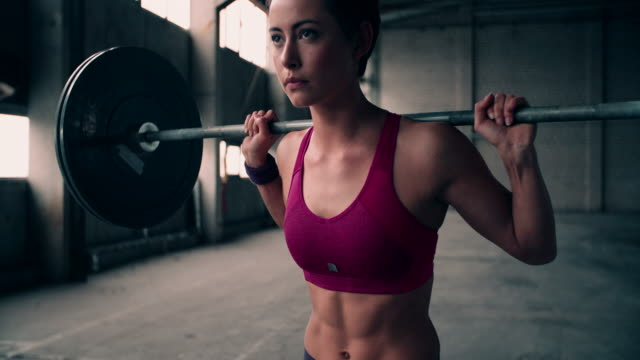 Young woman resting a heavy barbell on her shoulders video