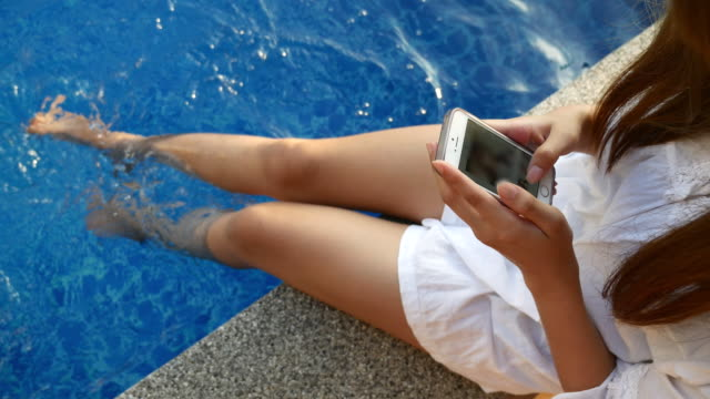 Young woman resting and using smartphone poolside video