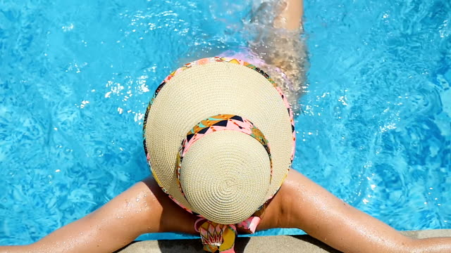 young woman resting in resort pool - cappello video stock e b–roll