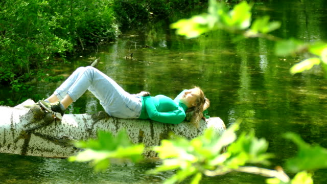 young woman resting in solitude on a forest river
