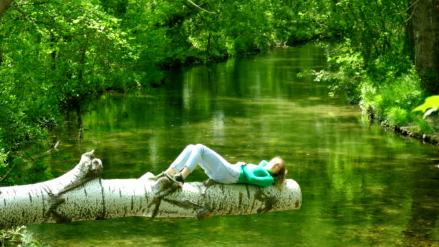 young woman resting in solitude on a log above a forest river