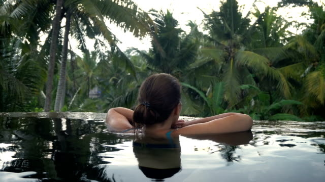 Young woman restingin the pool in the tropical garden video